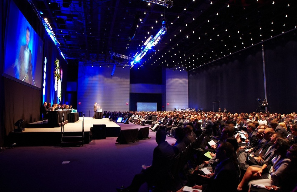 Photo of a speaker panel and audience in a large conference auditorium