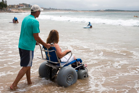 Photo of a man pushing a person in a wheelchair into the water.